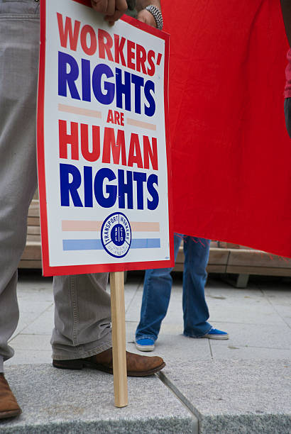 "Workers' Rights ""Dallas, Texas, United States - May 1, 2011: A demonstrator holds a pro-workers' rights sign from the AFL-CIO during a May Day protest in downtown Dallas. May Day is International Workers' Day and is often used to promote Socalism, Communism, and other leftist ideologies."" labor union stock pictures, royalty-free photos & images"