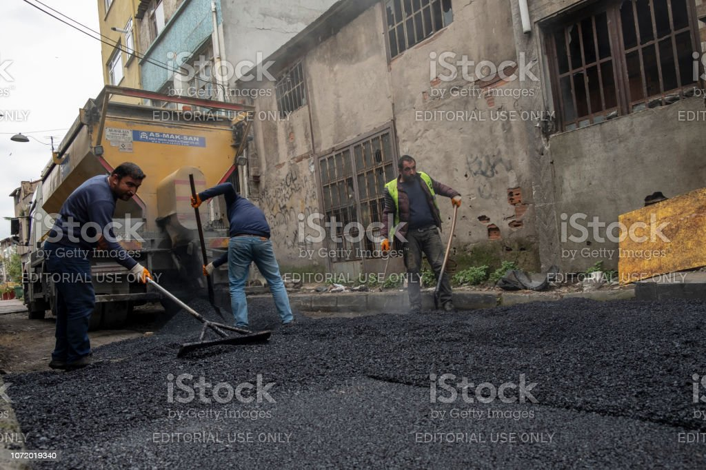 İşçiler, silindir ve yol inşaat ve onarma işleri sırasında çalışma Asfalt Finişer makine. stok fotoğrafı