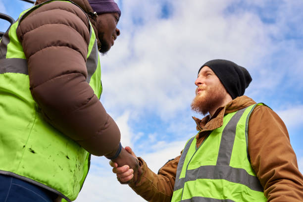 Workers Shaking Hands Outdoors Low angle portrait of two industrial workers wearing reflective jackets shaking hands outdoors against cold blue sky frontier field stock pictures, royalty-free photos & images