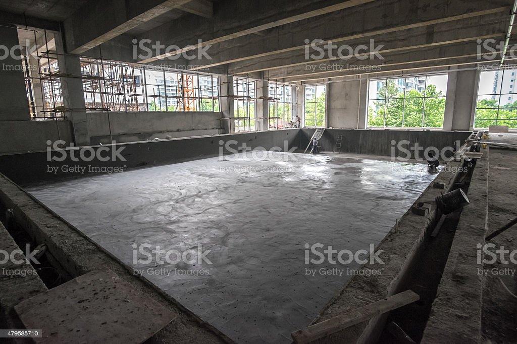 Arbeitnehmer glättende nassen Zement in riesigen, leeren Pool – Foto