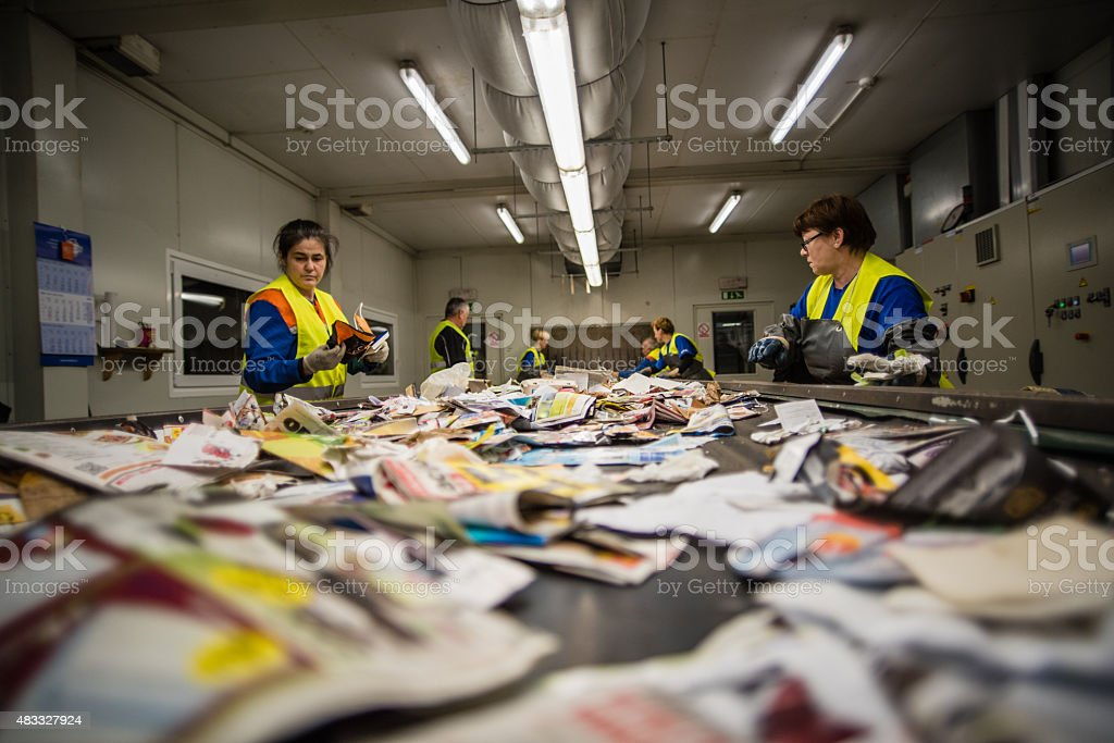 Workers sorting papers at recycling plant stock photo