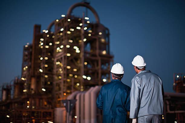arbeiter stehend in ölraffinerie - baugenehmigung stock-fotos und bilder