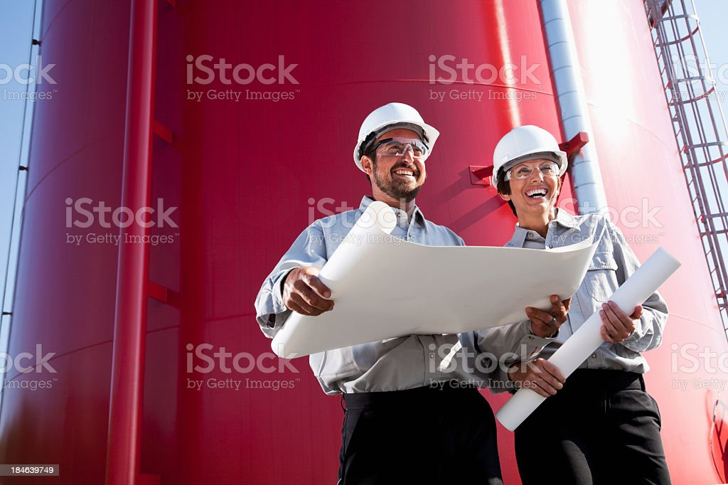 Workers standing by industrial water tower with plans royalty-free stock photo