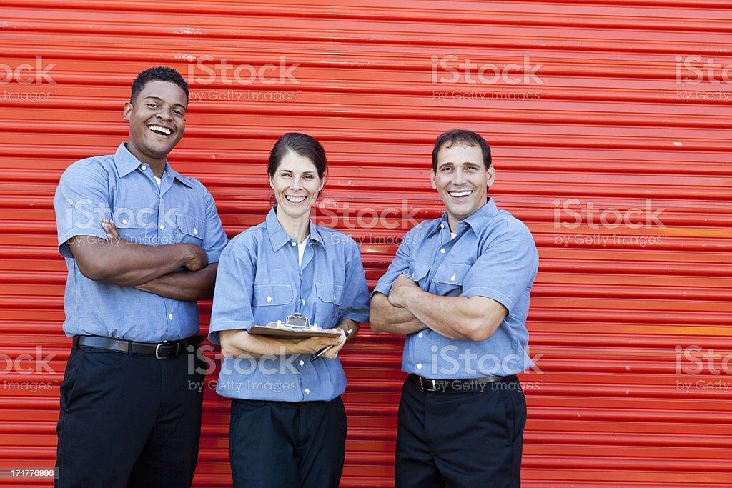 Workers standing in front of metal door stock photo