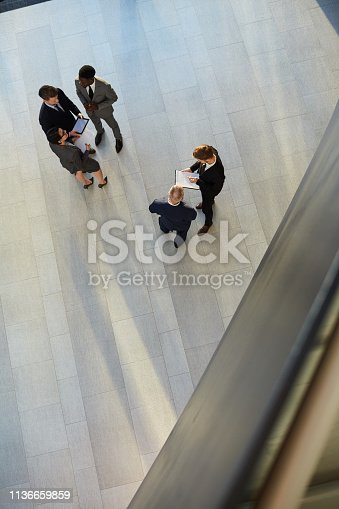 From above of businesspeople standing in group in modern hall of office having discussion