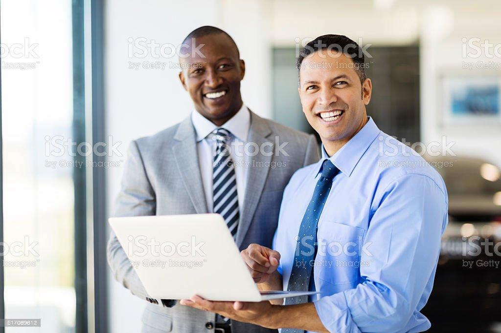 workers standing inside car showroom stock photo