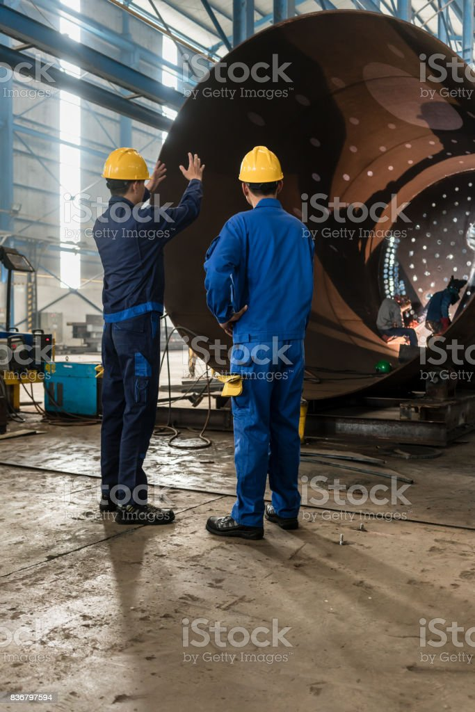 Workers supervising the manufacture of a metallic cylinder stock photo