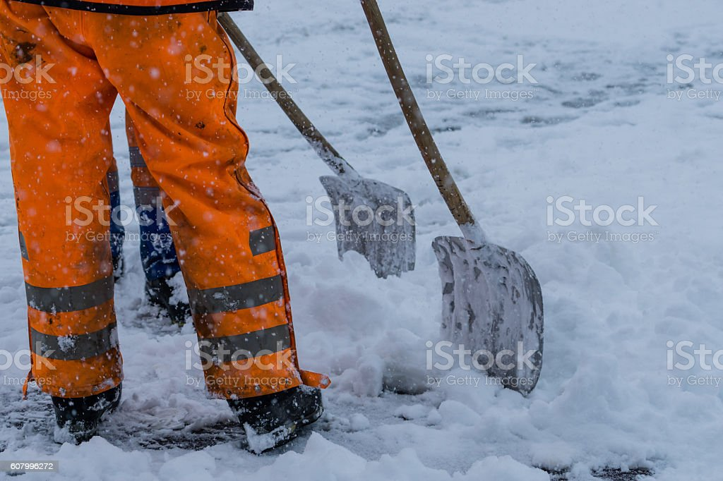 Workers sweep snow from road in winter stock photo