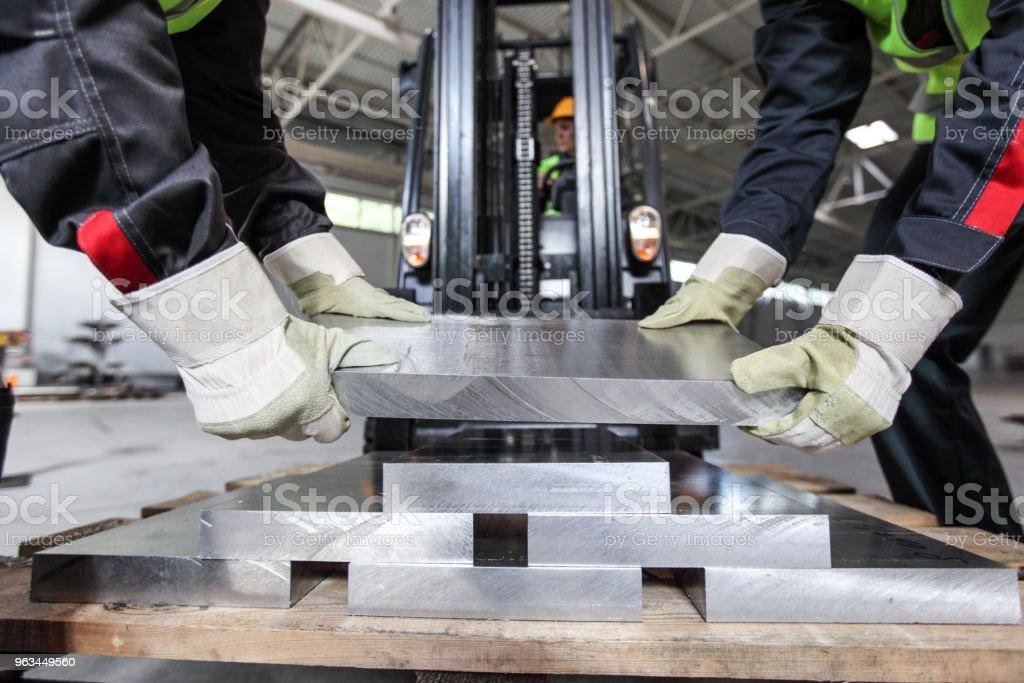 Workers taking aluminium billet - Zbiór zdjęć royalty-free (Aluminium)