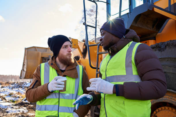 Workers Taking Break in Cold Portrait of two workers, one African-American, drinking coffee and chatting next to heavy industrial truck on worksite frontier field stock pictures, royalty-free photos & images