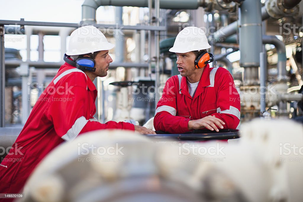 Workers talking at chemical plant stock photo