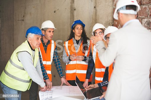 istock Workers talking at construction site 692208334