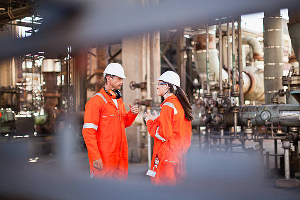 workers talking at oil refinery - refinery stock photos and pictures