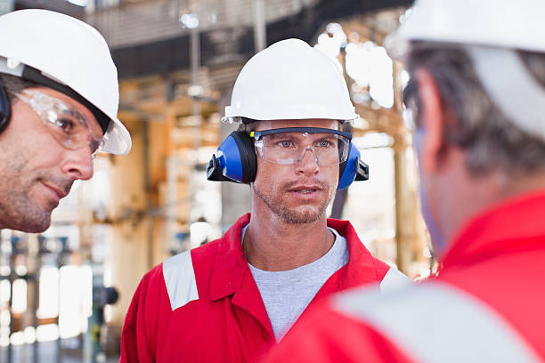 Workers talking at oil refinery  protective eyewear stock pictures, royalty-free photos & images