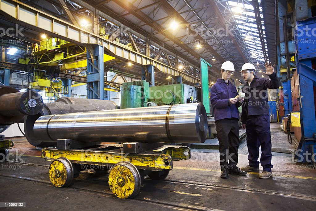 Workers talking in steel forge stock photo