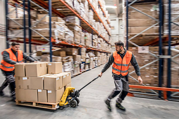 Workers transporting boxes in warehouse Two workers transporting boxes in warehouse. pallet jack stock pictures, royalty-free photos & images