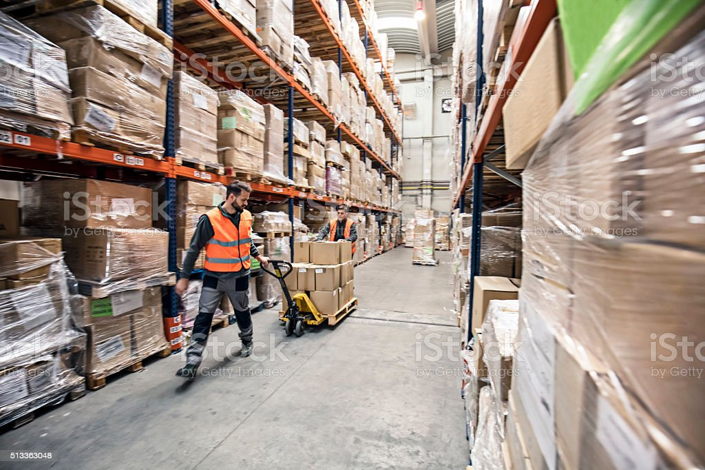 Workers transporting boxes in warehouse stock photo