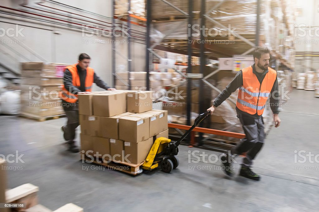 Workers transporting cardboard boxes in warehouse stock photo