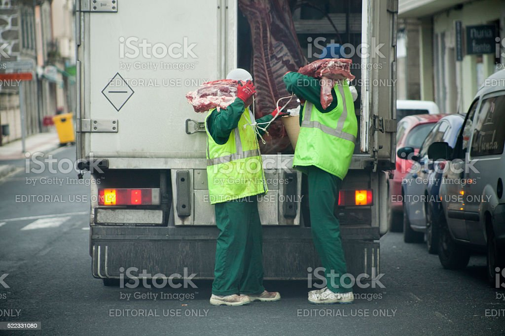 Workers unloading meat delivery truck. stock photo