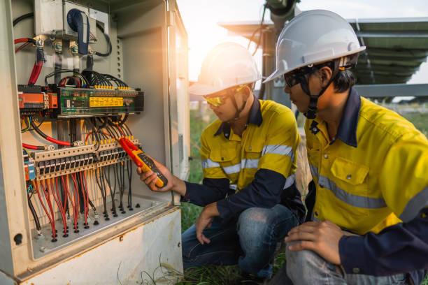pracownicy używają miernika zaciskowego do pomiaru prądu przewodów elektrycznych wytwarzanych z energii słonecznej w celu potwierdzenia normalnego prądu - elektryczność zdjęcia i obrazy z banku zdjęć