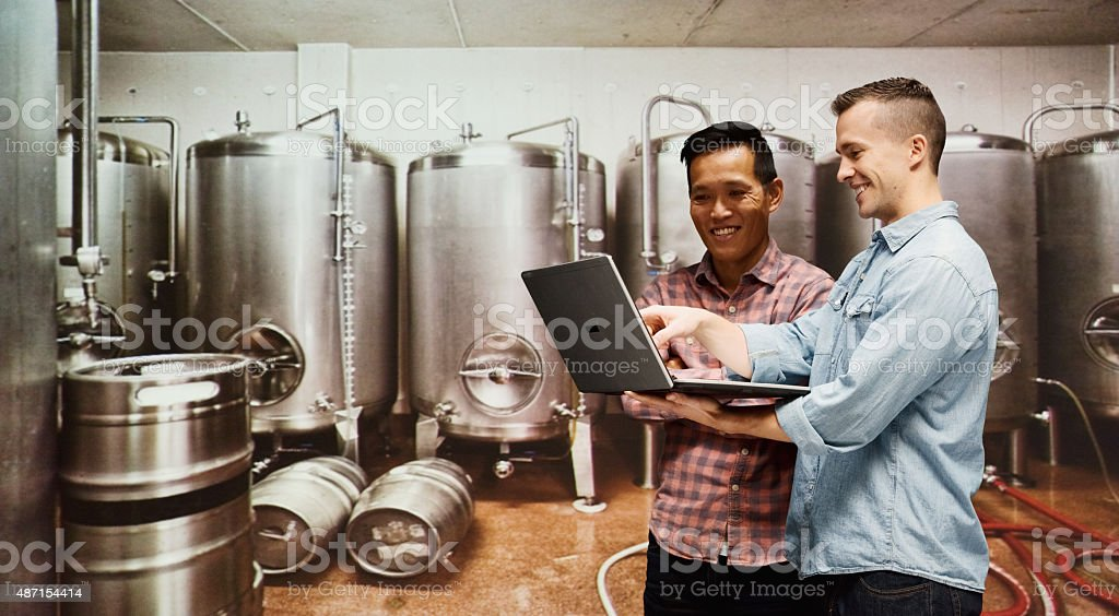 Workers using laptop in brewing plant stock photo