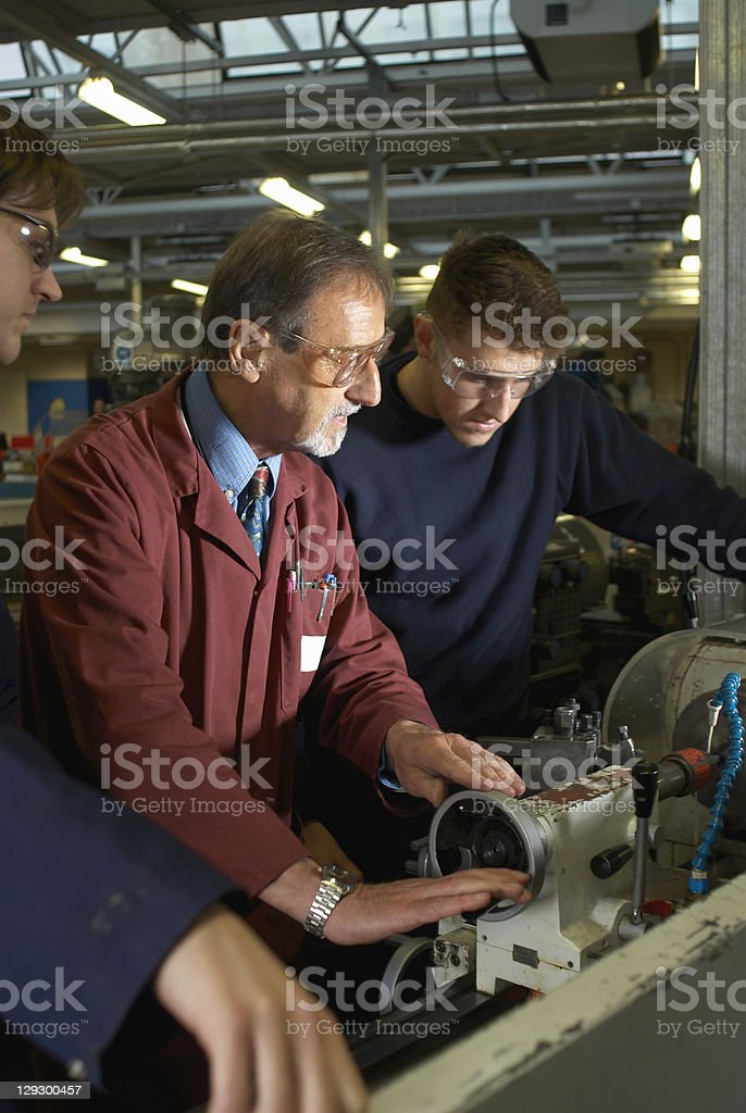 Workers using machinery in factory stock photo