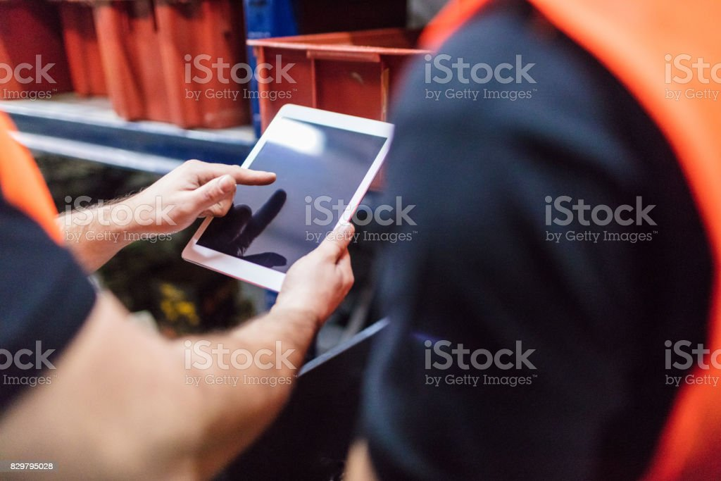Workers using tablet computer at factory warehouse stock photo
