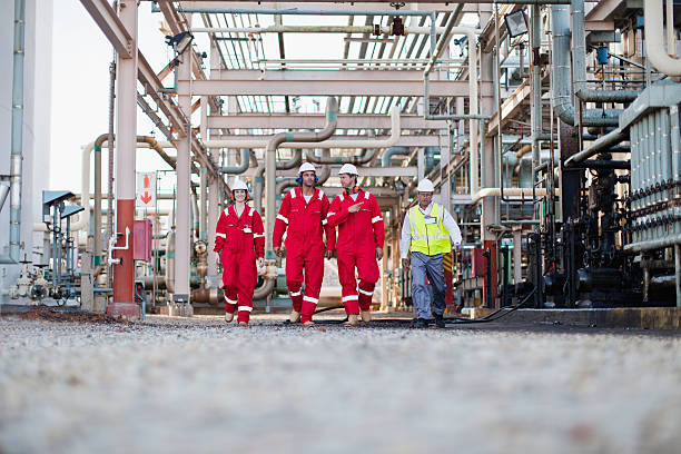 workers walking at chemical plant - refinery stock photos and pictures