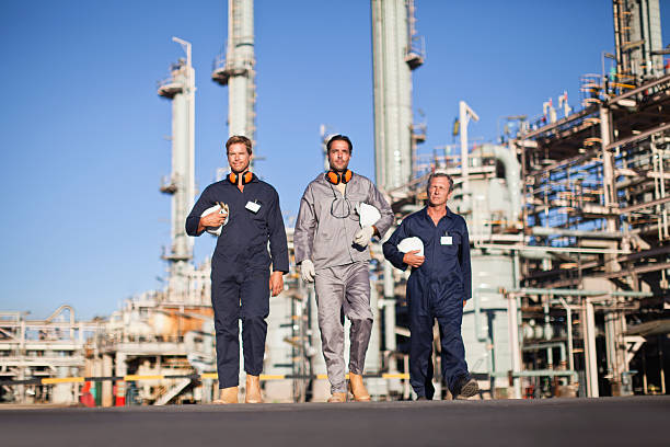 workers walking at oil refinery - after work stock photos and pictures