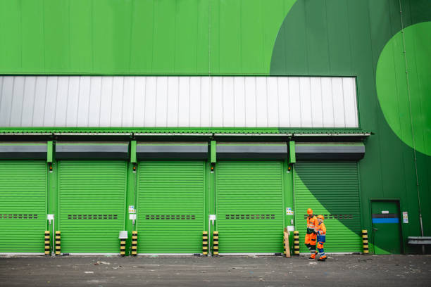 Workers Walking in Recycling Facility Loading Dock Area Distant viewpoint of male and female waste reduction workers in protective suits and hardhats walking through recycling facility loading dock. social responsibility stock pictures, royalty-free photos & images