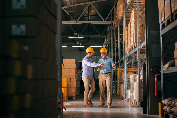 Workers walking in storage and pointing at boxes. In hands folder and tablet, on heads helmets. stock photo
