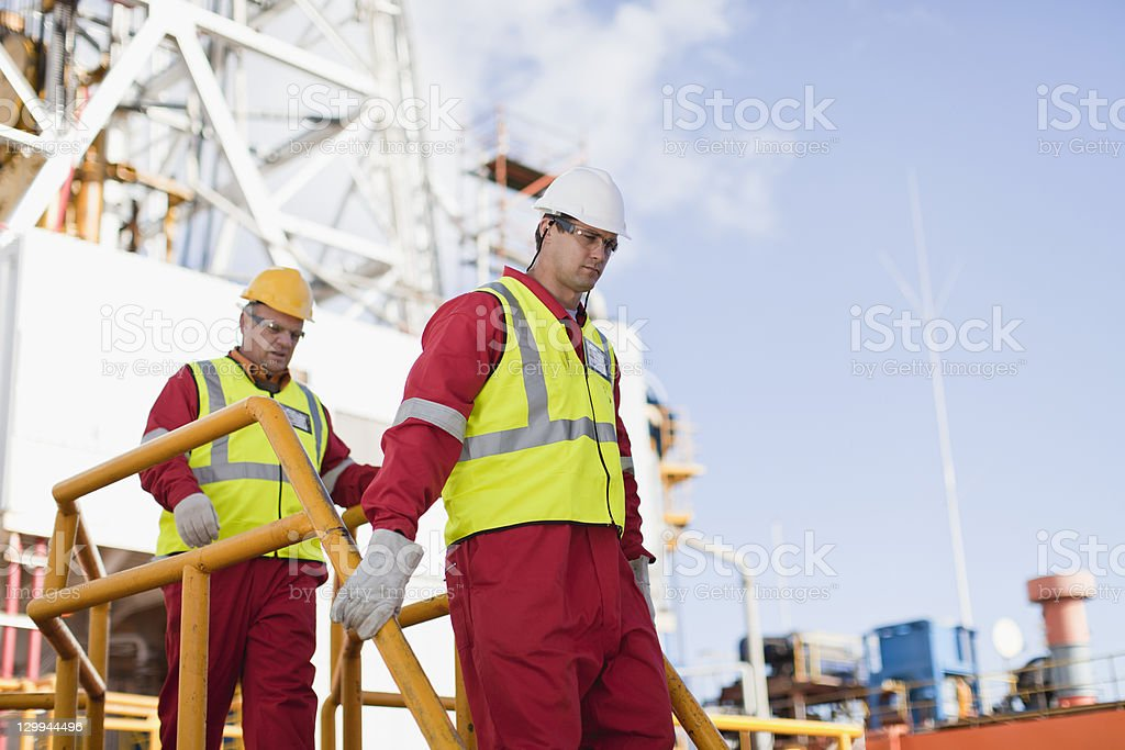 Workers walking on oil rig stock photo