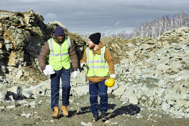 Workers walking on Site in Alaska Full length portrait of two industrial  workers wearing reflective jackets, one of them African, walking on mining worksite outdoors, copy space frontier field stock pictures, royalty-free photos & images