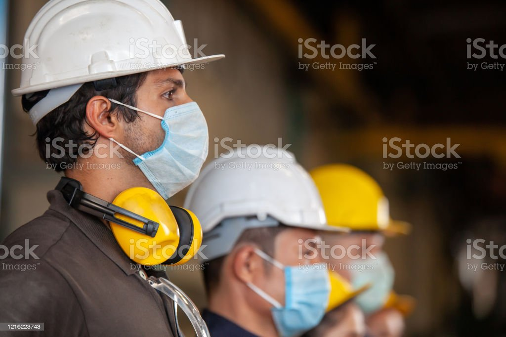 Workers wear protective face masks for safety in machine industrial factory. Workers wear protective face masks for safety in machine industrial factory. Asia Stock Photo
