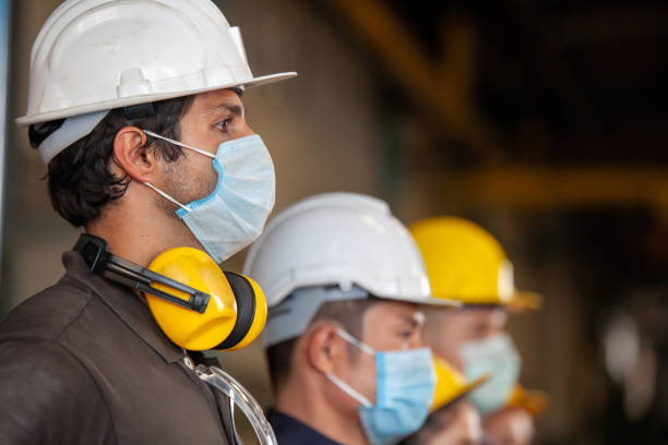 Workers wear protective face masks for safety in machine industrial factory. Workers wear protective face masks for safety in machine industrial factory. covid mask stock pictures, royalty-free photos & images