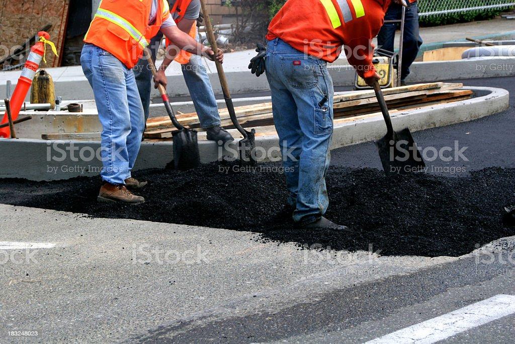 Workers wearing jeans shoveling asphalt over older pavement stock photo