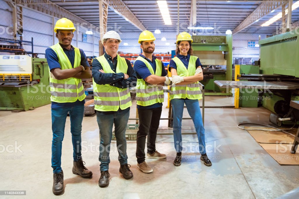 Workers with arms crossed standing in factory Full length of production workers with arms crossed working in manufacturing company. Engineers are wearing reflective clothing and hardhats. They are in factory. 20-24 Years Stock Photo