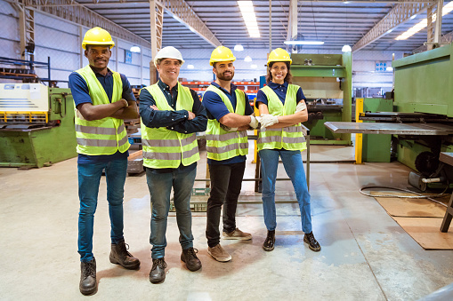 Workers With Arms Crossed Standing In Factory Stock Photo - Download Image Now