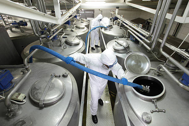 workers with blue hoses, filling large silver tanks in plant stock photo