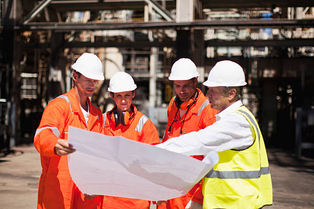 Workers with blueprints at oil refinery  power occupation stock pictures, royalty-free photos & images