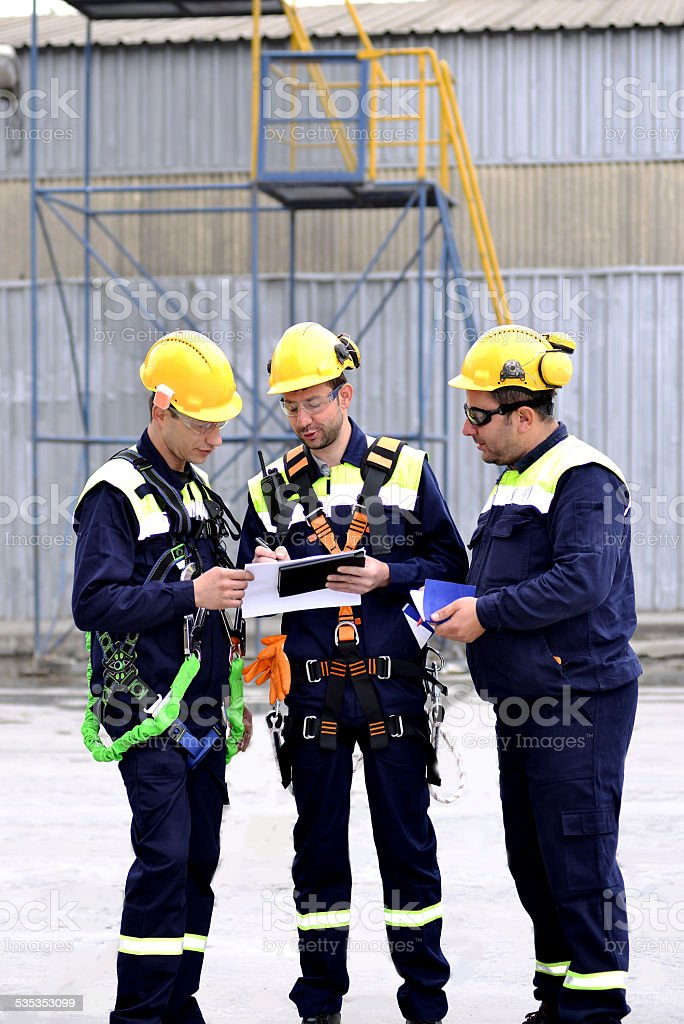 Workers with climbing equipment looking at work plan stock photo