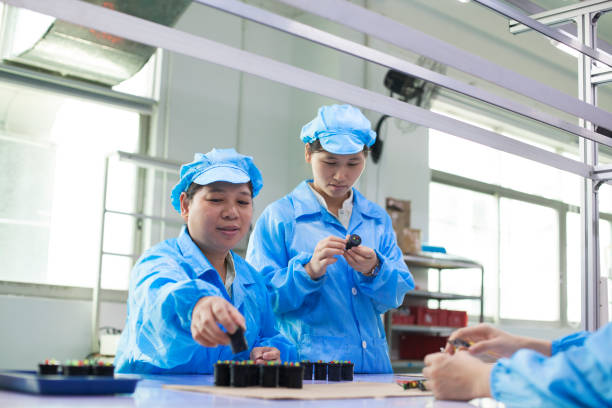 Workers with diodes in uniforms at a LED lighting factory in Dongguan, China stock photo