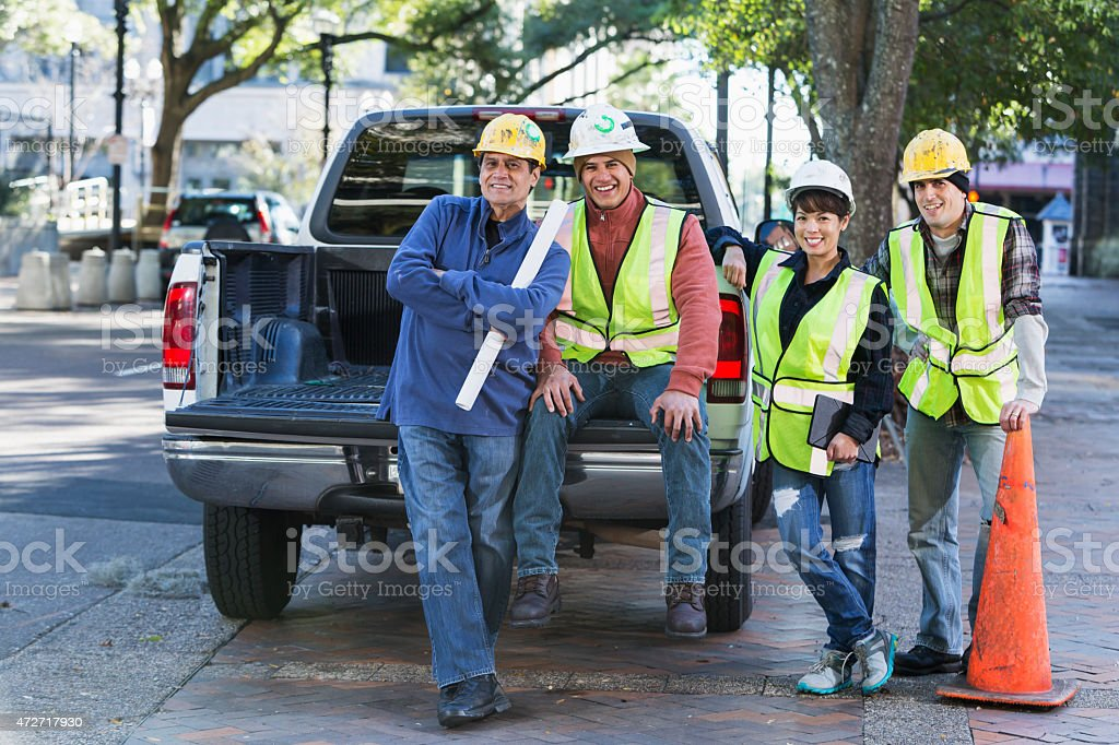 Workers with hard hats and safety vest in city stock photo