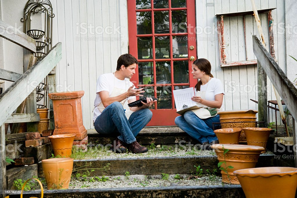 Workers with laptop and clipboard talking on back door steps stock photo