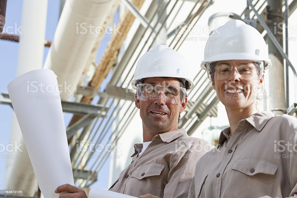 Workers with plans at manufacturing plant royalty-free stock photo