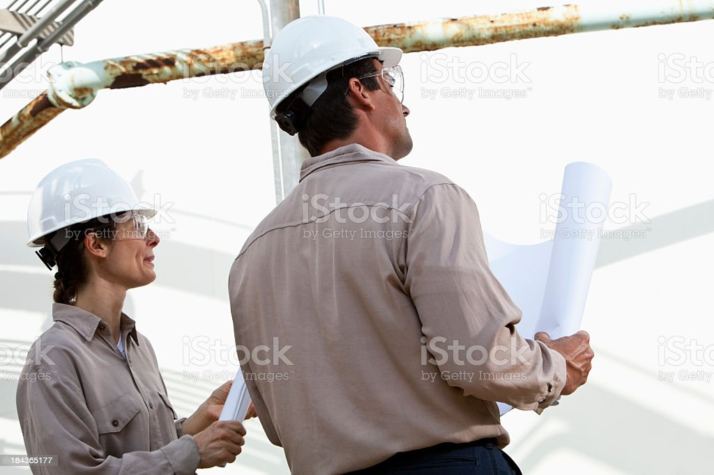 Workers with plans at manufacturing plant stock photo