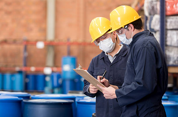 Workers working at a chemical plant Team of workers at a chemical plant doing inventory and writing on a clipboard while wearing protective wear chemical plant stock pictures, royalty-free photos & images