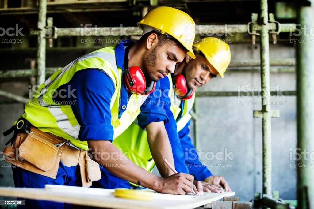 Workers working at construction site ストックフォト