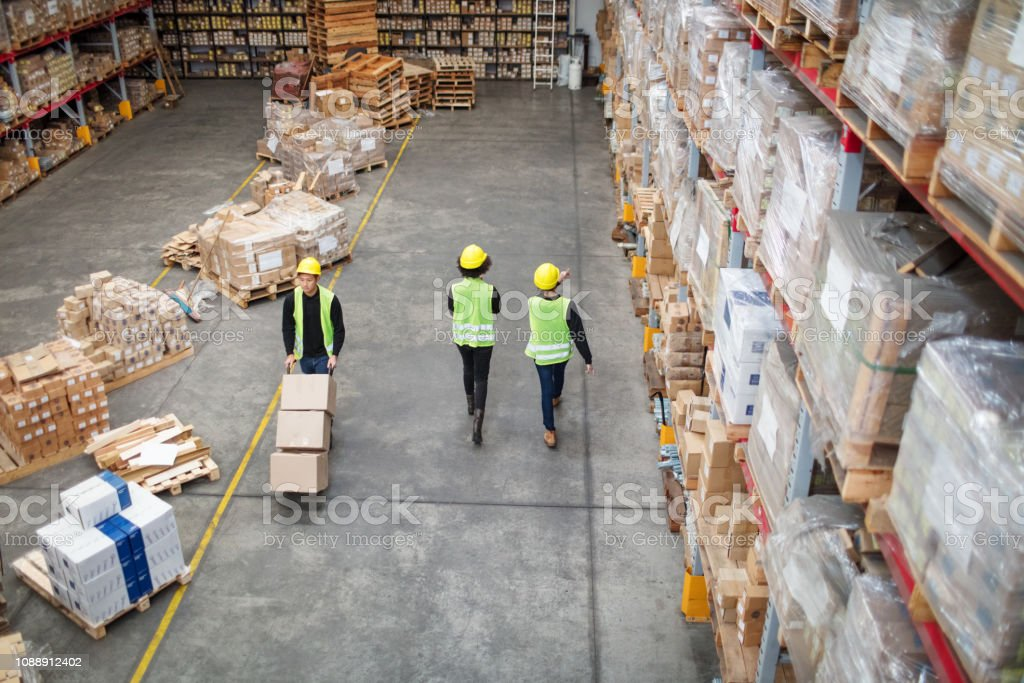 Workers working in large warehouse stock photo