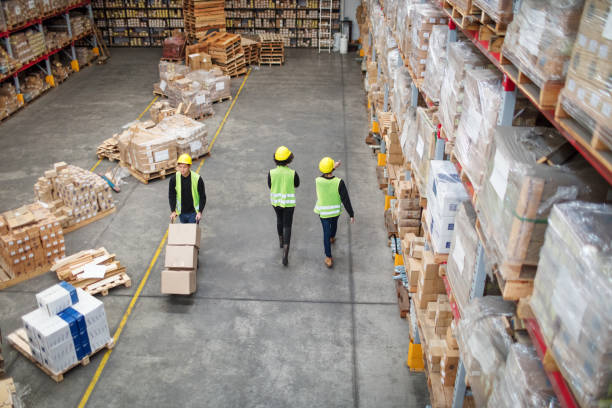 Workers working in large warehouse Workers working in large warehouse. Man moving boxed in a trolley with tow colleagues walking by in a distribution warehouse. warehouse interior stock pictures, royalty-free photos & images